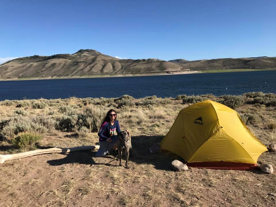 woman and dog at campsite